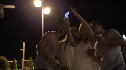 Friends making mobile selfie in night street Footage