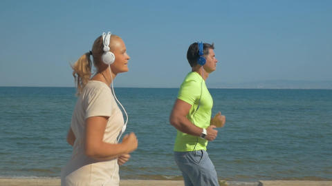 Couple in headphones jogging along the sea front Footage
