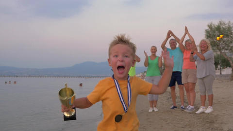 Happy little winner running with trophy Footage