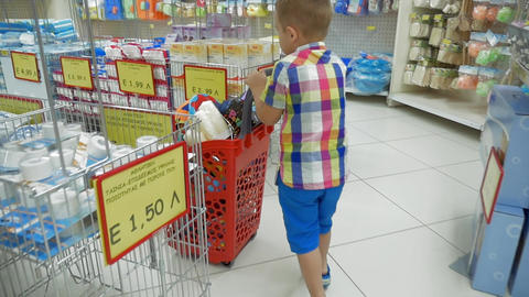 Little boy rolling shopping cart in supermarket Footage