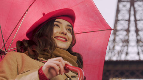 Young woman with umbrella flirting, looking for acquaintance, smiling to man Footage