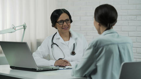 Friendly doctor talking to patient, promising to help, informing good results Live Action