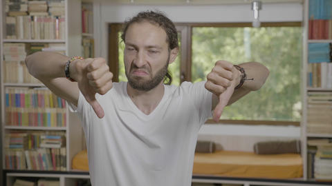 Disgusted man having negative reaction showing thumbs down disapproving Live Action