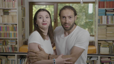 Scared reaction of young couple embracing each other expressing fear and shock Footage