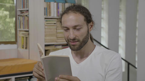 Hipster student man having fun reading an interesting book expressing amazement Footage