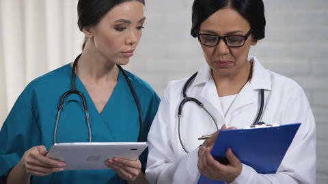 Doctor and nurse discussing test results, inserting information into tablet Footage