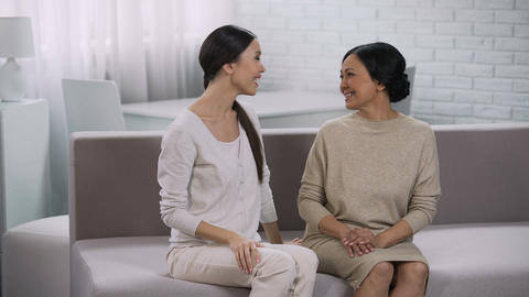 Two women happily communicating, smiling and embracing, trust in relationship Live Action