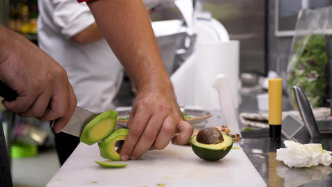 Cutting avocado in pieces on a cutting board Live Action