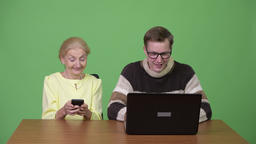 Senior businesswoman using phone and young handsome man using laptop together Footage