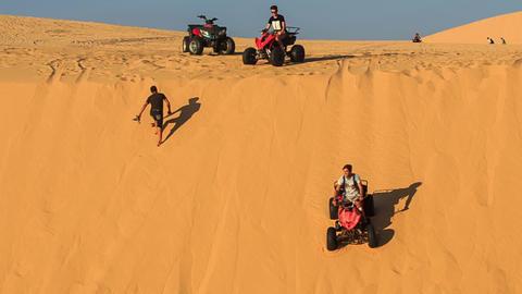 Tourists Run Quads down Dune Crest Guy Climbs GIF