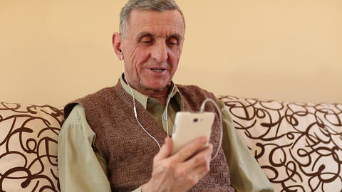 Senior man communicates through a smartphone Man with mobile phone Footage