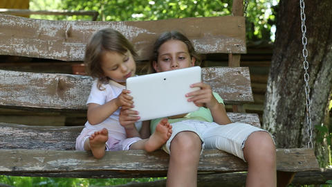 Two girls with tablet computer sits on the swing bench Footage