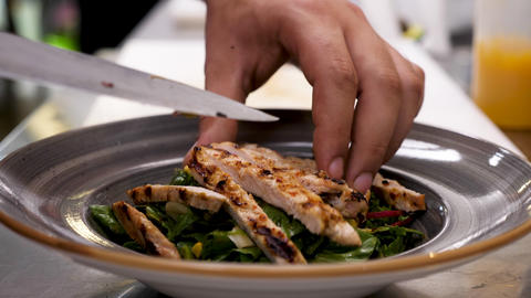 Cook hands placing fresh grilled meat on plate with avocado salad Live Action