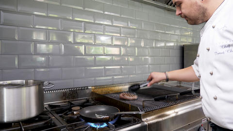Cook placing a piece of grilled beef meat from the grill to a pan Live Action