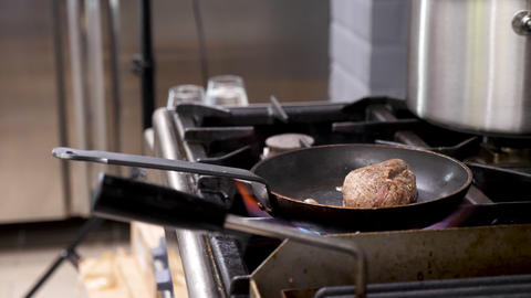 Piece of beef meat frying on pan in a stove ビデオ