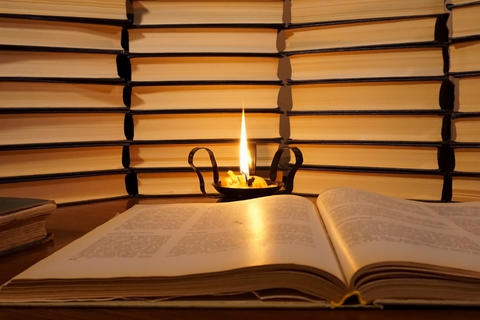 Open book and a burning candle Fotografía