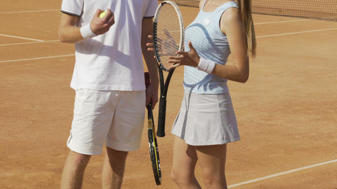 Man and woman in sportswear standing on tennis court and flirting, sports hobby Footage