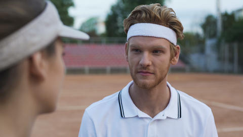 Funny redheaded male winking and flirting with beautiful female at tennis court Footage