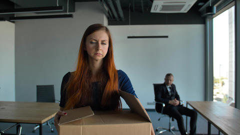 Sad employee packing her belongings and leaving the office after being fired 영상물