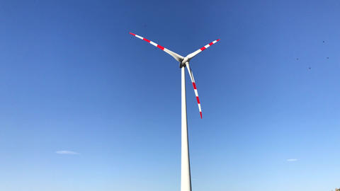 Rotating blades of wind turbine towers in blue sky ビデオ