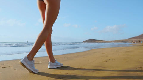 Close-up of leg sporty woman in white sneakers running along beautiful sandy Footage