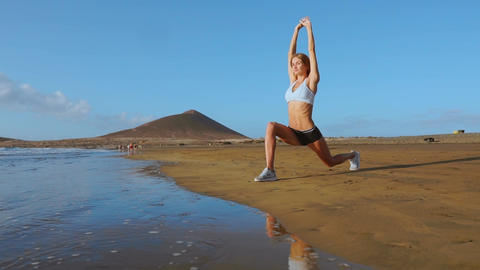 Yoga retreat and training - woman in yoga pose at beach at sunrise. Female yoga Footage
