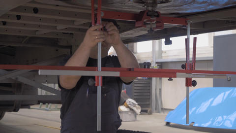 auto mechanic checks axle stabilizer truck Live Action