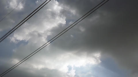 Gray overcast clouds on blue sky before rain or storm. Power lines in the sky ビデオ