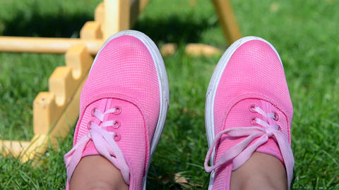Girl in pink moccasins resting on green grass in summer ビデオ