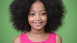 Young cute African girl with Afro hair smiling against green background Footage