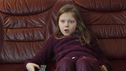 Young, funny girl is watching TV at home. Face expression Footage