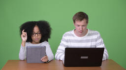 Young African girl and young Scandinavian man using gadgets together Footage