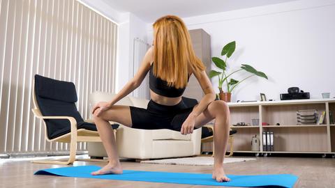 Arabian mixed race woman stretching and taking the goddess yoga pose 영상물
