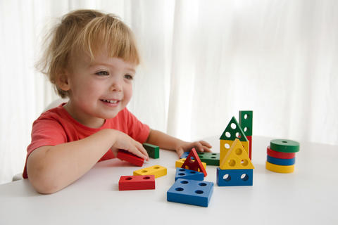 Little boy playing with colorful block フォト