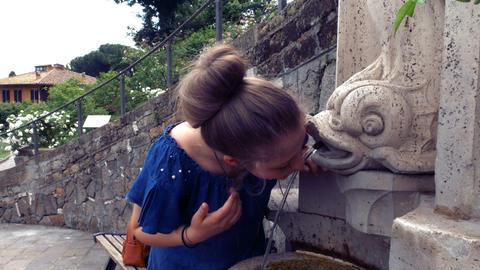 teenage girl drinks water from a fountain in Rome GIF