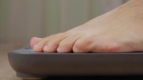 Extreme closeup of barefoot woman weighting on scale, side view Live Action