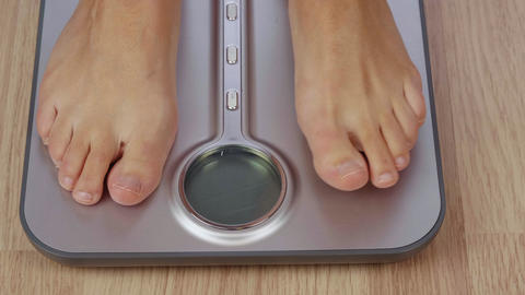 Partial view of barefoot woman weighting on electronic scale with display GIF