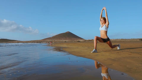 Woman doing leg stretches. Fitness girl stretching legs on beach training. SLOW Live Action