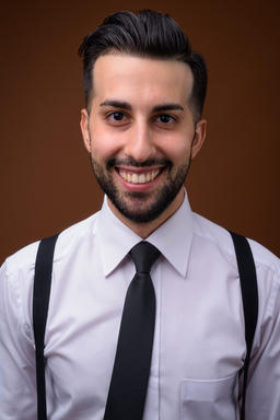 Young handsome bearded Iranian businessman against brown backgro Photo