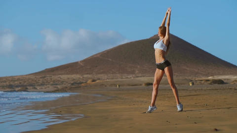 Yoga woman poses at beach working out and relaxing outside on beach at sunrise Live Action