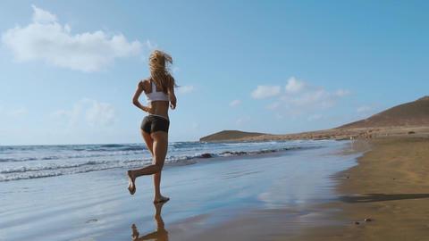 Beautiful sportive woman running along beautiful sandy beach, healthy lifestyle Live Action