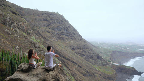 A man and a woman sitting on top of a mountain looking at the ocean sitting on a Live Action