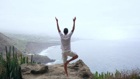 Fit young man practices sun salutation yoga in mountain for ocean. Young man Live Action
