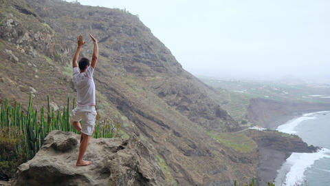 Fit young man practices sun salutation yoga in mountain for ocean. Young man Footage