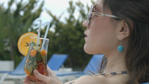Girl enjoying taste of cool cocktail sitting by pool of her luxurious mansion Footage