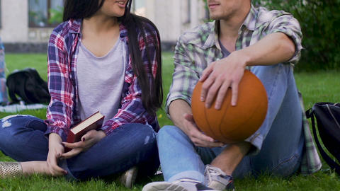 Girl with book, guy with basketball ball sitting grass and talking, relationship Live Action