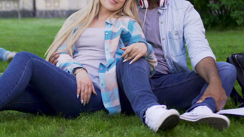 Young couple sitting on grass together, girl leaning against guy, relationship Live Action