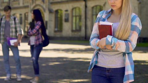 Lonely female student looking at classmates talking, unshared love, loneliness Footage