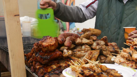 Man frying greasy meat on grill at street festival, harmful unhealthy junk food Live Action