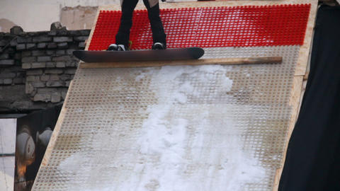 Mischievous youth showing snowboarding tricks, preparing for competition Live Action